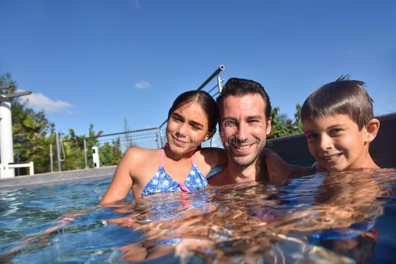 生与孩子获得乐趣在游泳池 免版税库存照片