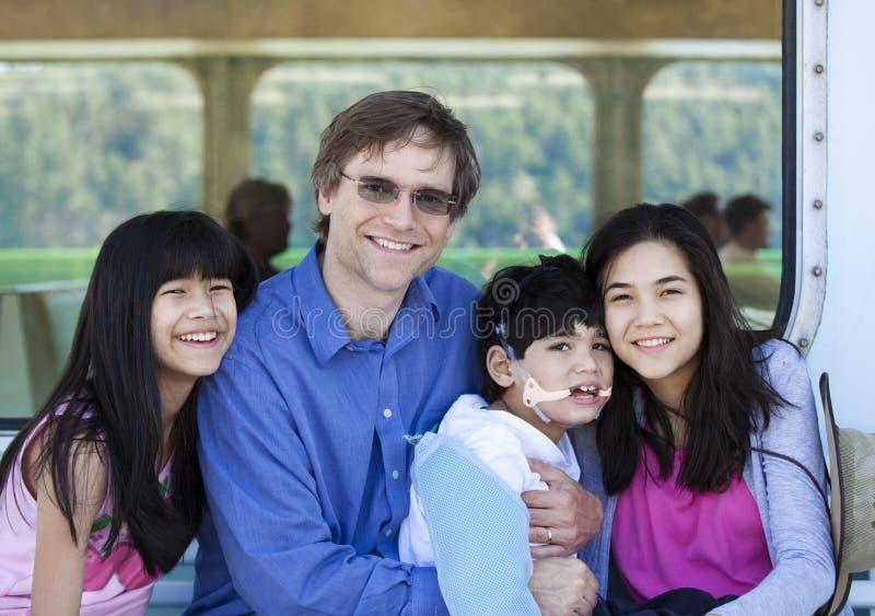 生与他两种人种的孩子,拿着轮渡的失去能力的儿子 免版税库存图片