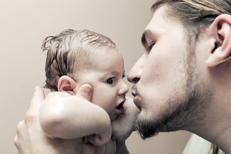 生与他的拥抱和亲吻他的年轻婴孩在面颊 库存照片