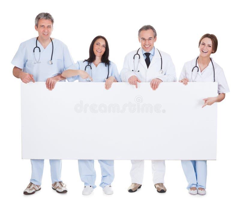 医生举行招贴的小组 免版税图库摄影
