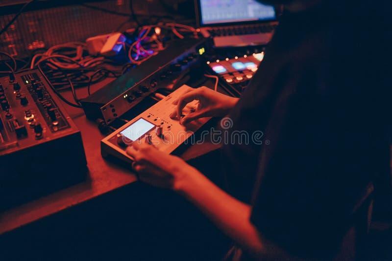 生产商DJ搅拌器在有发光的戏剧音乐吹捧Dubstep电子恍惚构成的一个夜总会与现代密地controlle 免版税库存照片