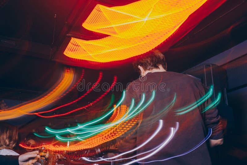 生产商DJ搅拌器在有发光的戏剧音乐吹捧Dubstep电子恍惚构成的一个夜总会与现代密地controlle 免版税图库摄影