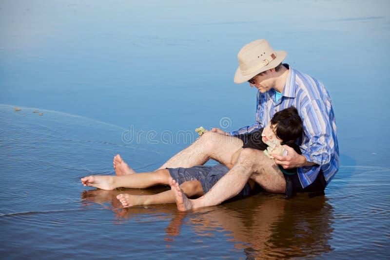 生使用与海滩的残疾儿子,拿着他直立的东西 免版税库存图片