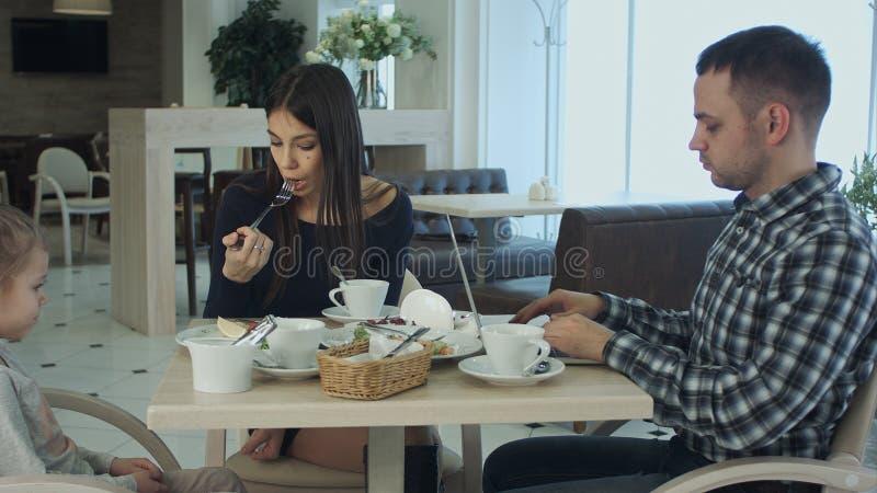 生使用他的膝上型计算机,当坐与他的妻子和女儿咖啡馆的时 妇女理解和不干扰他 库存图片