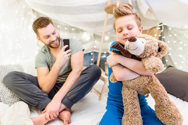生使用智能手机,当拥抱与玩具熊时的小儿子 免版税图库摄影