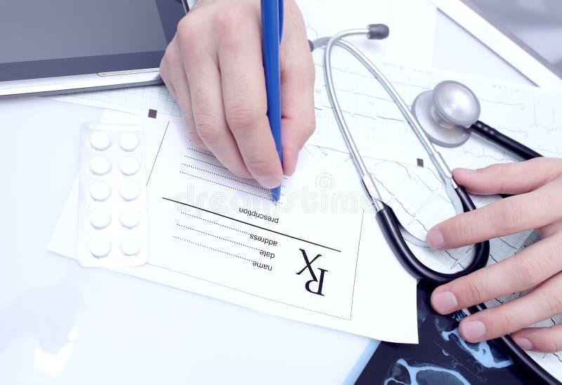 医生写一张处方在他的书桌 免版税图库摄影