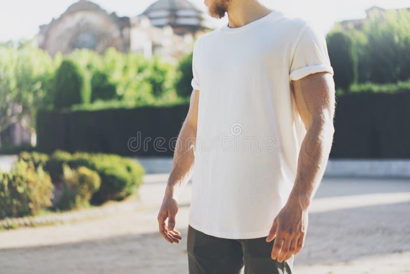 生动描述有胡子的肌肉人佩带的白色空白的T恤杉 在日落的绿色城市庭院背景 水平的大模型 库存照片