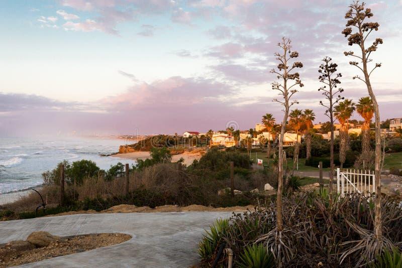 生动的五颜六色的晚上日落海岸村庄镇视图 库存图片
