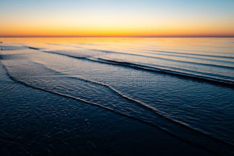 生动的惊人的日落在波罗的海国家-黄昏在有天际的海由太阳照亮 免版税库存照片