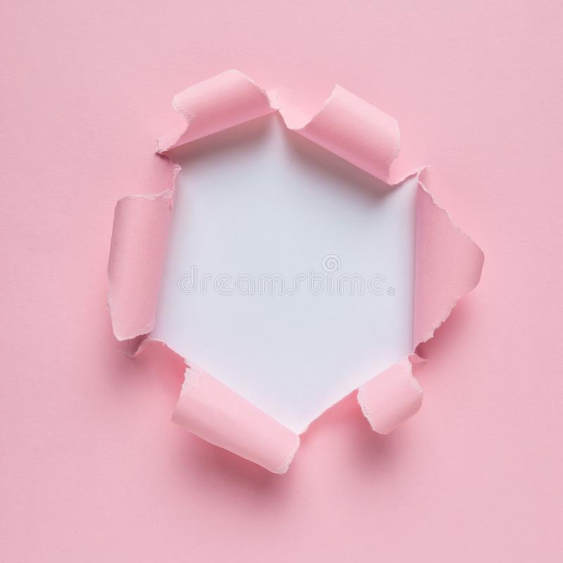 生动的桃红色被剥去的纸有破裂的孔背景 库存图片
