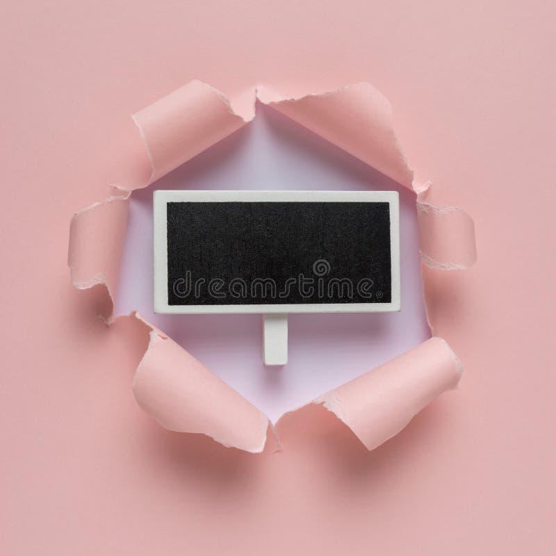 生动的桃红色被剥去的纸有破裂的孔背景 免版税库存图片