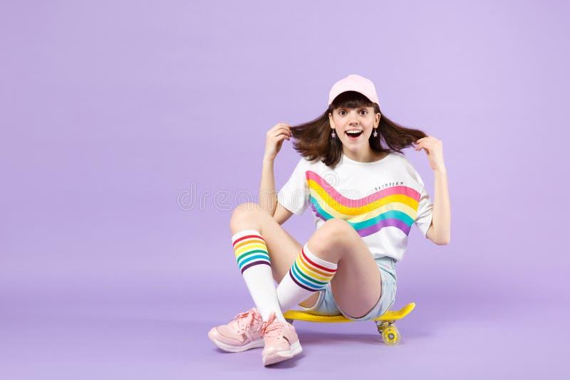 生动的衣裳的激动的青少年的女孩坐黄色滑板,保持嘴开放被隔绝在紫罗兰色淡色墙壁上 库存照片