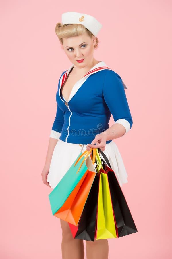 生命有色的购物袋的样式夫人在玫瑰色背景 购物时间画报在演播室称呼了女孩 免版税库存图片