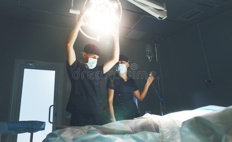 医生和助理为手术做准备在手术室 免版税图库摄影