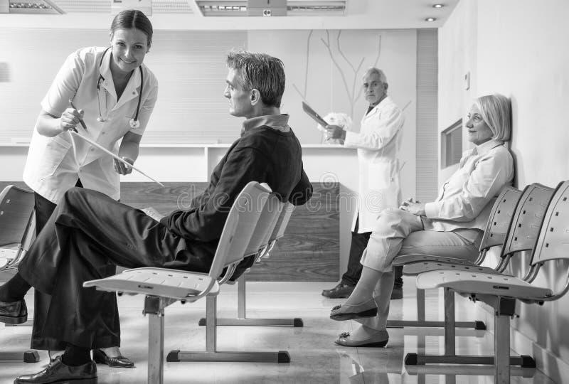 医生和患者在医院候诊室 免版税图库摄影