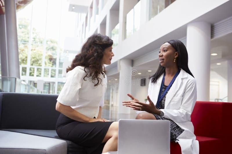 医生和患者开会议在医院接纳地区 免版税库存图片