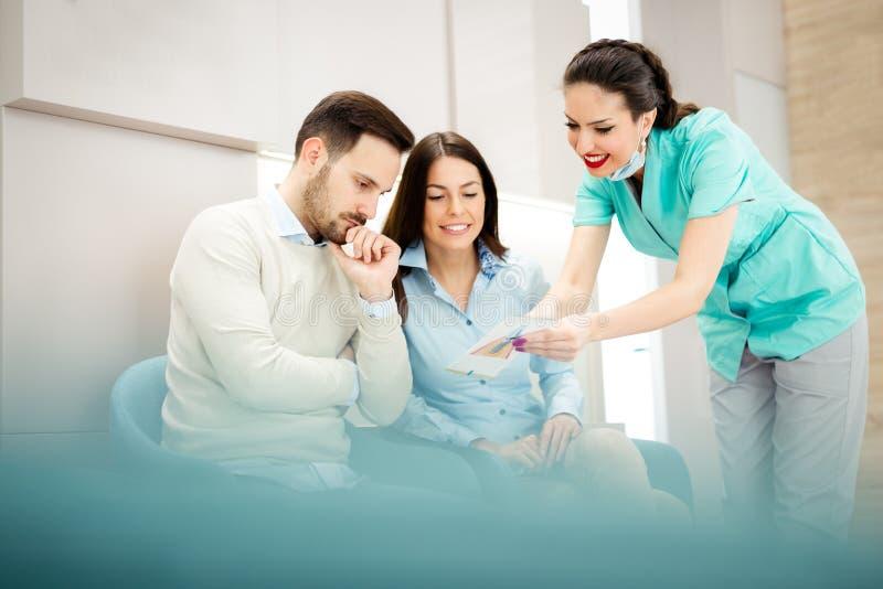 医生和患者讲话在医院候诊室 免版税图库摄影