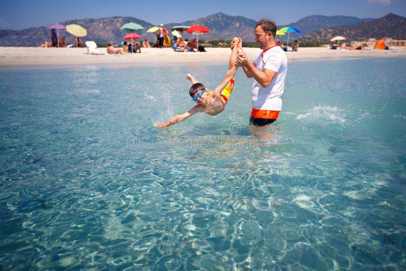 生和获得他的小的儿子在海滩的乐趣 免版税图库摄影