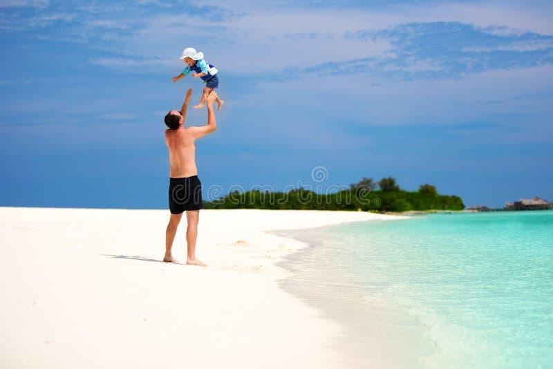 生和获得他的小的儿子在海滩的乐趣 图库摄影