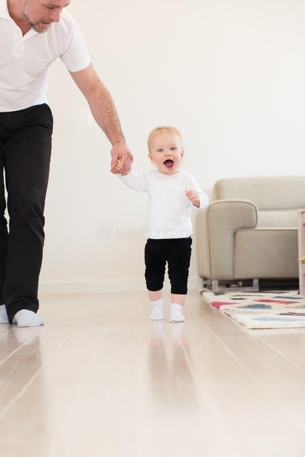 生和他演奏和学会如何的美丽的女婴走 图库摄影