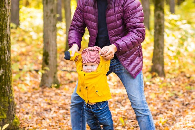 生和他的小儿子获得乐趣在秋天公园 库存图片