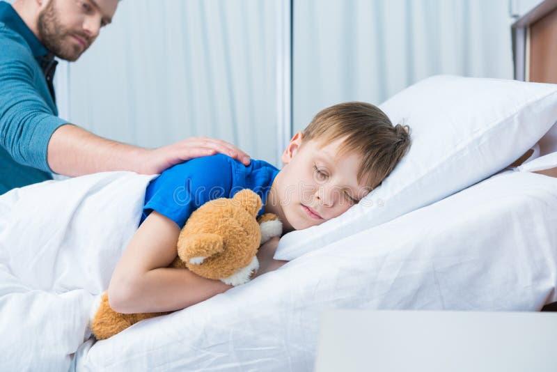 生在与玩具熊的医院病床上的感人的病的矮小的儿子 库存照片
