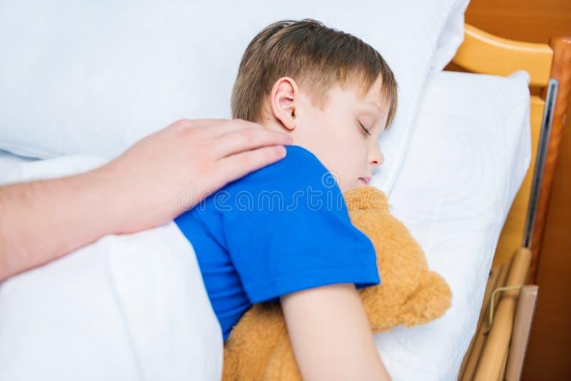 生在与玩具熊的医院病床上的感人的病的矮小的儿子 图库摄影