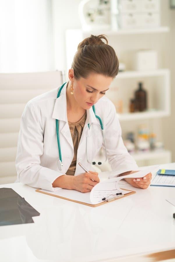 医生在剪贴板的妇女文字 库存图片