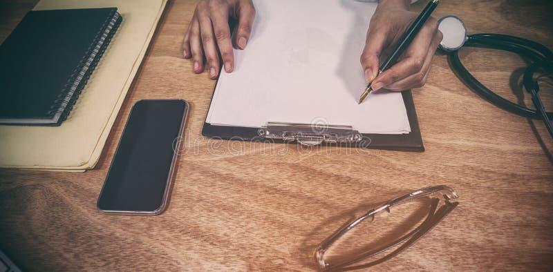 医生在剪贴板的文字处方的播种的手在书桌 库存照片