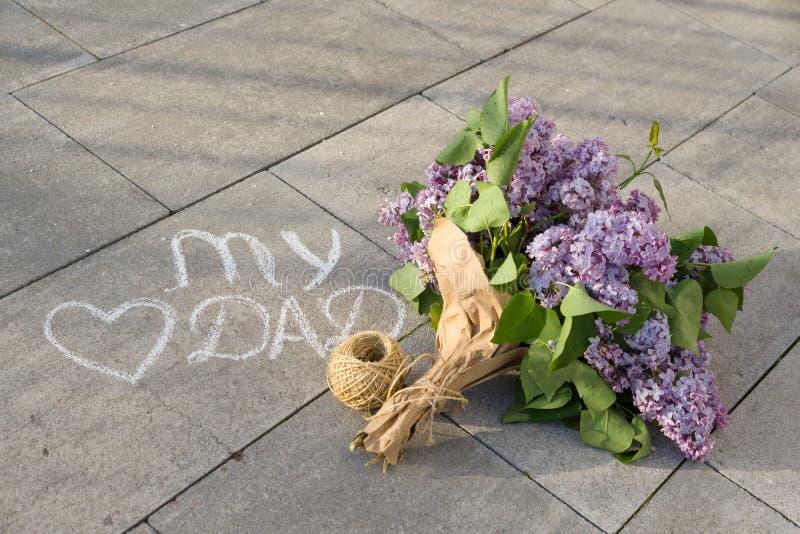 生在沥青的` s天问候概念手写的文本-我的爱爸爸和心脏与淡紫色花花束  免版税库存图片
