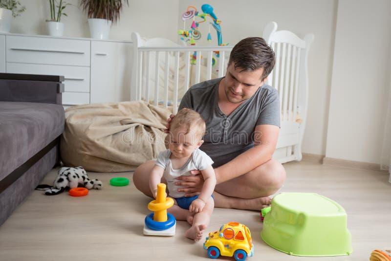 生坐与他的男婴的地板和使用与玩具 免版税库存图片