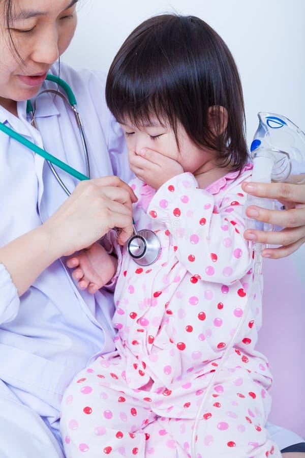 医生帮助一点亚洲女孩采取呼吸,吸入Th 库存图片