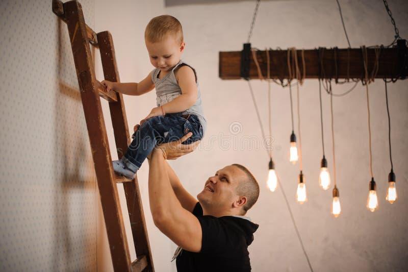 生帮助他的爬上梯子的小儿子 免版税库存图片