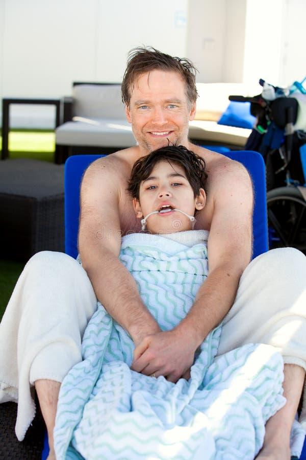 生干燥在与残疾儿子的蓝色懒人边  免版税库存照片