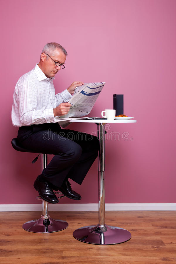 生意人咖啡馆坐的报纸读取 库存图片