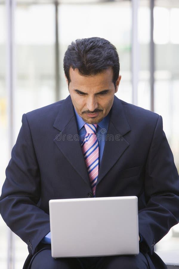 生意人外面计算机膝上型计算机使用 免版税库存图片