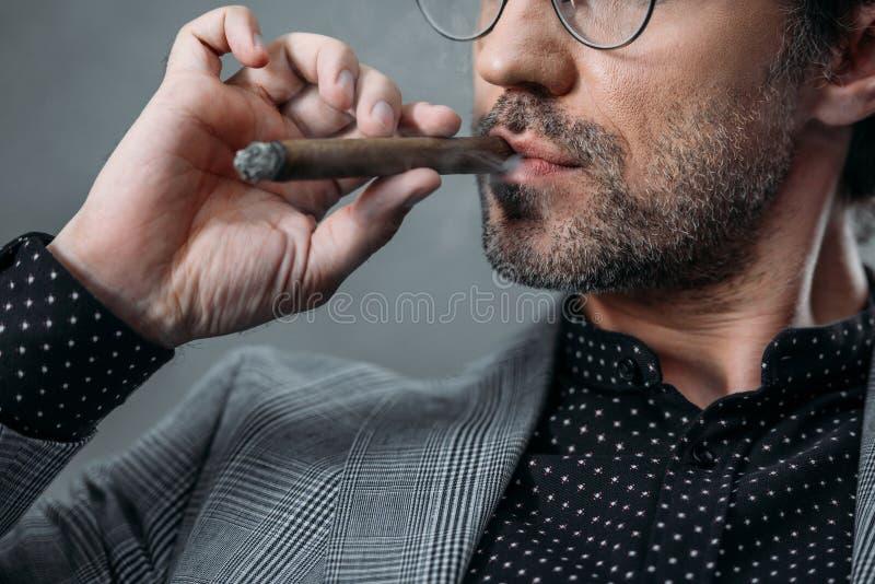 生意人抽烟的雪茄 免版税库存图片