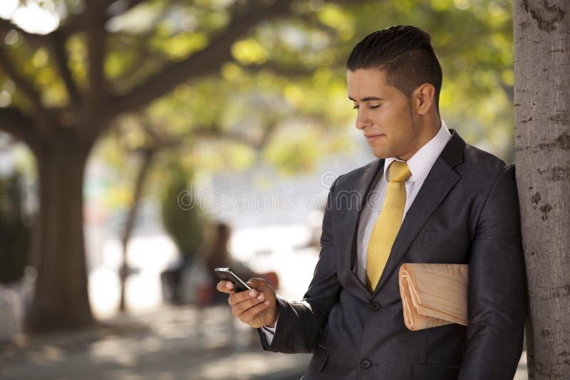 生意人放松在结构树旁边的在城市公园,发送嘘 免版税图库摄影