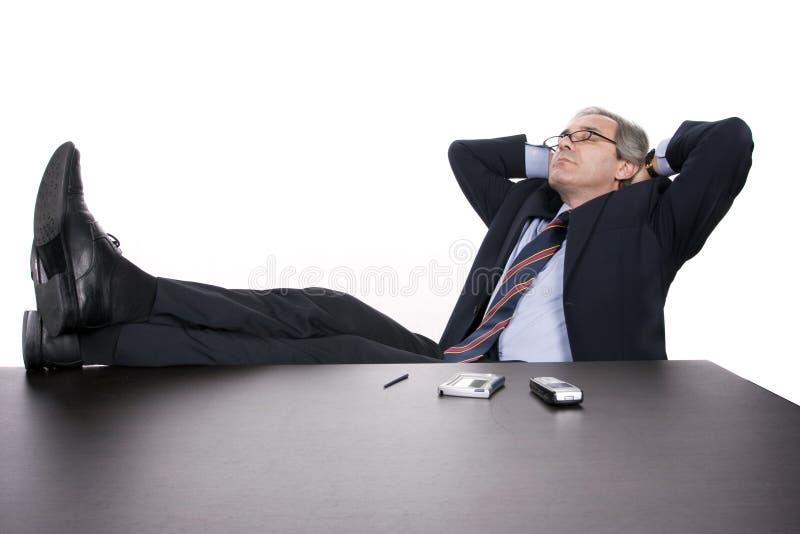 生意人服务台他的在放松成功 免版税库存照片