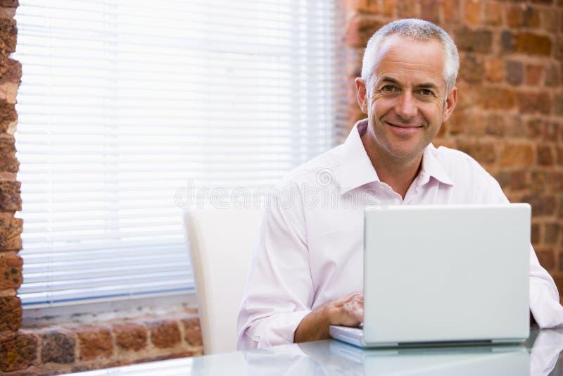 生意人膝上型计算机办公室坐的微笑 免版税库存照片