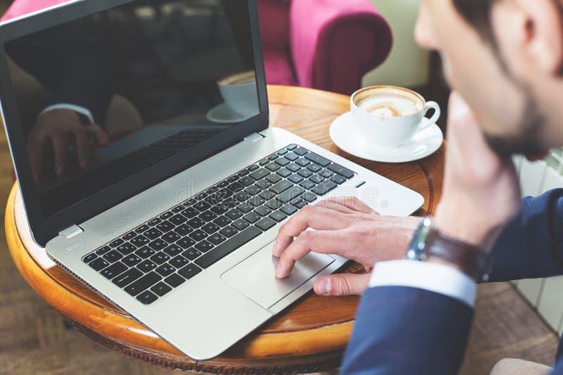 生意人膝上型计算机运作的年轻人 库存图片