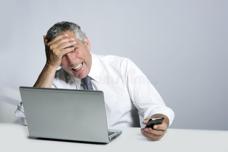 生意人计算机姿态笑的电话前辈 免版税图库摄影