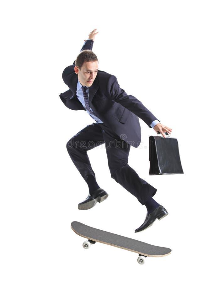 生意人跳的滑板 免版税库存照片