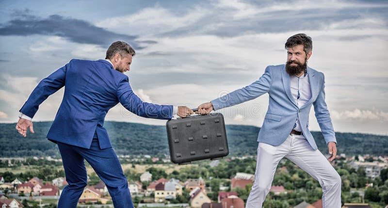 生意风景背景 商人从商务伙伴拿走公文包 欺骗和强夺概念 图库摄影