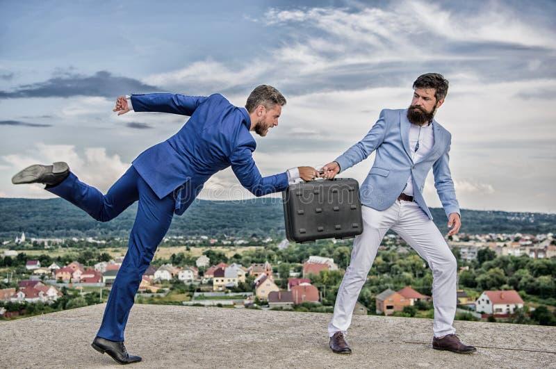 生意风景背景 商人从商务伙伴拿走公文包 欺骗和强夺概念 库存图片