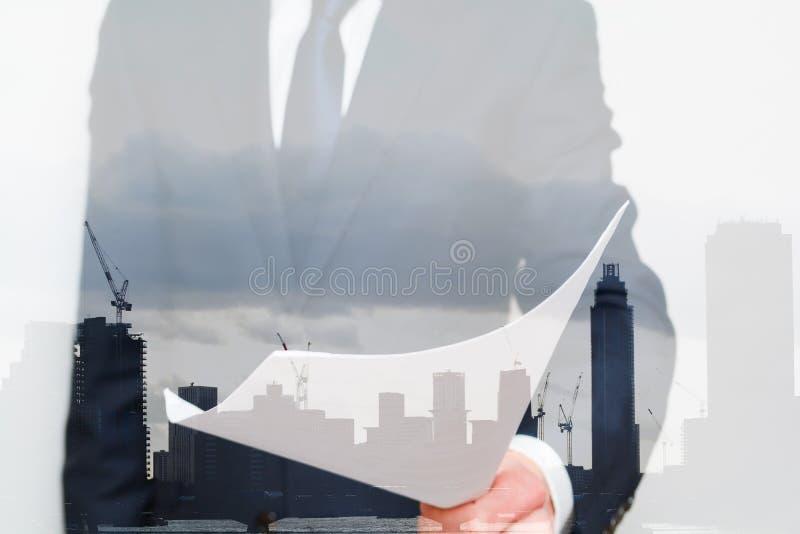 生意,拿着在现代办公楼都市风景前面的西装的人一个合同 人提供事务 免版税图库摄影