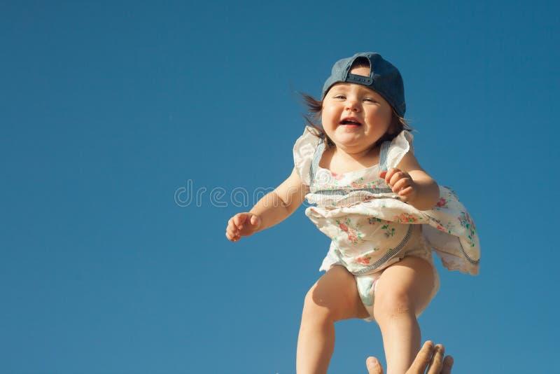 生扔他的小女儿在天空中 在晴天 免版税库存照片