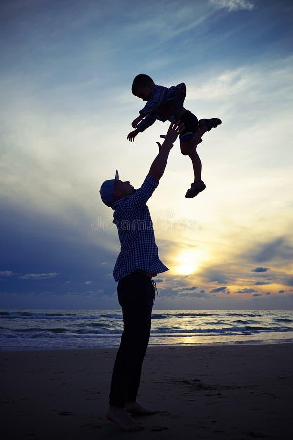 生扔孩子在海滩的日落 免版税库存图片
