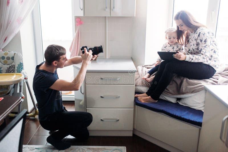 生拍他的女儿和妻子照片  免版税库存照片