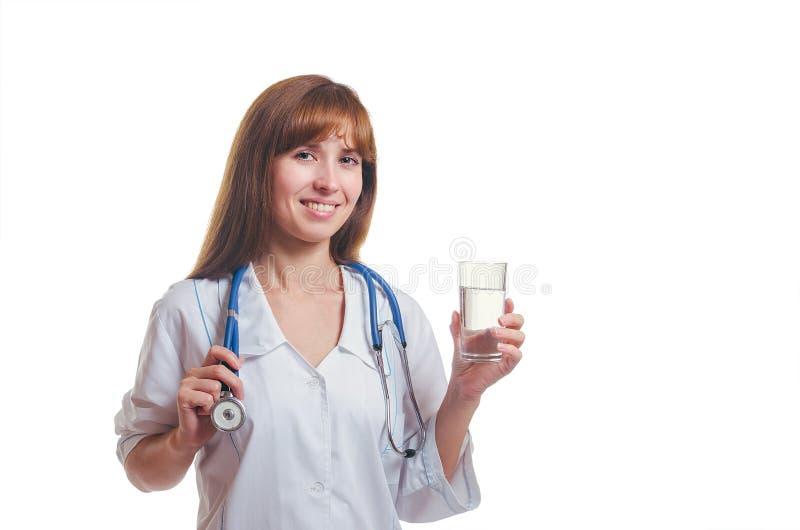 医生拿着一块玻璃用水手中并且微笑 库存图片